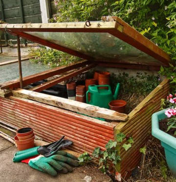 Gardeners Cold frame in the garden, used to protect seedlings from frost during winter