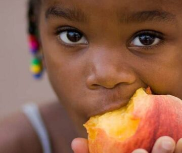 young girl eating a peach