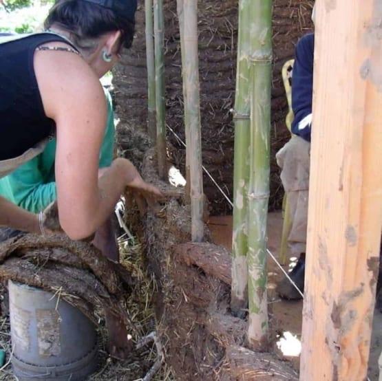 woman building cob house