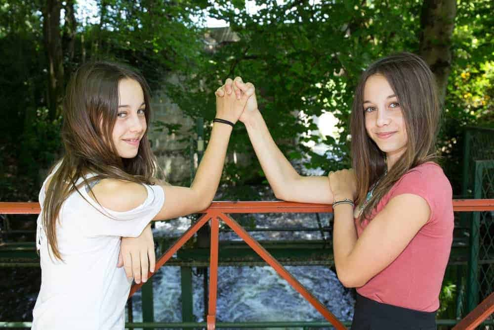 teenage sisters holding hands