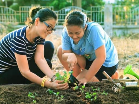 two teenage girls planting vegetables in a community garden