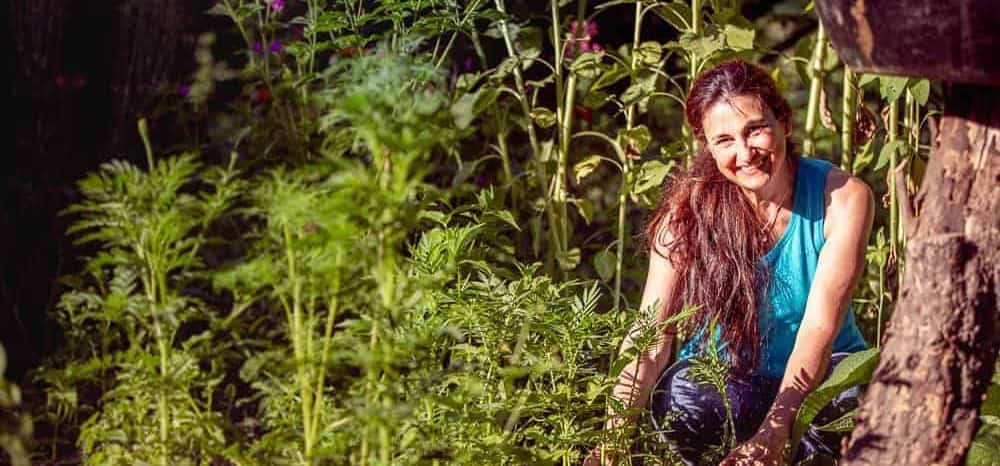 beautiful Spanish woman in organic garden with trees flowers and birdbath